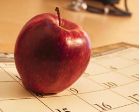 Apple sitting on calendar.